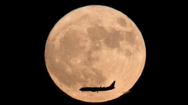 a-plane-flies-across-the-moon-seen-from-beijing-china